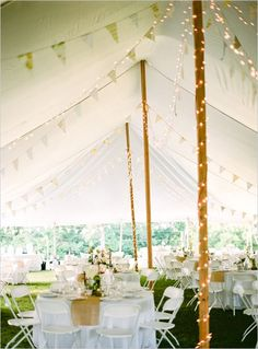 Pair bunting with lights to enhance the look of the tent for a backyard wedding. Love.