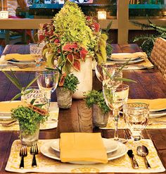 Yellow cloth napkins and place mats are the perfect way to update your table for summer. Small potted herbs serve as place cards and add an organic element to the table.