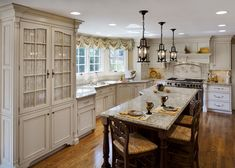 French country done right. Fabric insets in the doors, off white cabinets, wrought iron lanterns, and gleaming hardwood floors.
