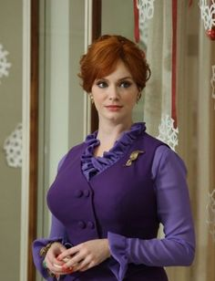 We barely saw Joan this episode, but she celebrated at the Sterling Cooper Christmas party with a lot of violet—a fit-and-flare party dress layered over a matching ruffled blouse, to be precise. Her purple ensemble was set off by a chunky gold charm bracelet and leaf-themed earrings and pin.
