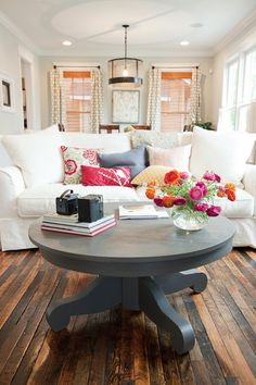 Gorgeous White Living Room with fabulous pops of color. In love with those floors!
