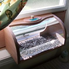Two-way mirrored panel lets you see the birds up-close and they cannot see you. Designed to sit inside the house, this feeder is easy to install. With our unique dove-tailed wood side panels, simply place the feeder on the windowsill and slide the panels out to fit the window. One inch thick wooden side panels provide great insulation and security. Easy to fill and clean from inside your home...