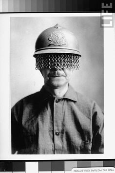 Mustachioed man wearing steel helmet w. built-on chain screen to protect soldiers' eyes from fragments of shell, rock, etc. during WWI