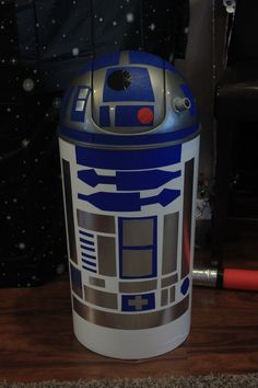 Artoo Detoo / R2D2  This guy made for an excellent Star Wars party photo prop.  I started with a grey garbage can from Big Lots $10.  I covered the body with White Magic sticky paper and used blue painter's tape and silver duct tape for the details.  The eye is made from a suction cup, plastic plumbing piece and a black marble.