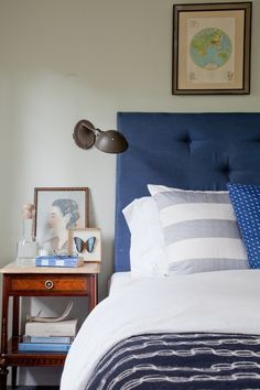 blue tufted headboard + sconce in bedroom by Emily Henderson