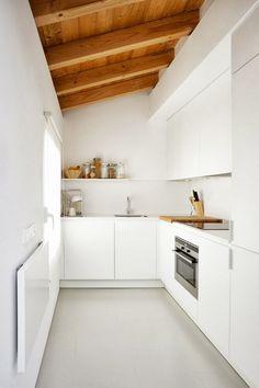 Discrete sleek white kitchen tucked in corner - decor with wood accents