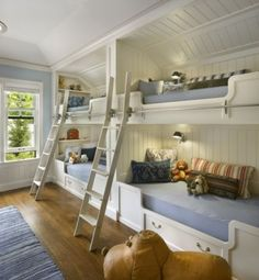 love this bunk room:  angled tray ceiling // built-in bunks // tongue + groove ceiling in nooks // great shade of blue // curved ladders // sconces // shelving // red + white ticking lumbar pillow // designer: Brian Snow