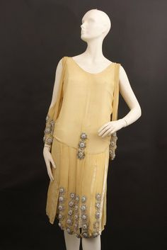 1920s pale yellow flapper dance dress with heavy diamante embellishments on a fine silk crepe de chine ground. The arm slips hang down the side of the dress looping over the shoulder to create embellishment to the side of the dress. Via Live Auctioneers.