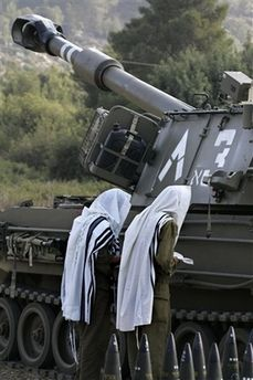 Israeli soldiers pray next to an artillery piece, near Shlomi, northern Israel, Saturday, July 22, 2006.
