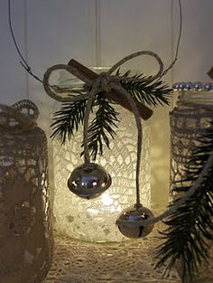 DIY Christmas Decoration - doilies, evergreen sprig, cinnamon stick, jingle bells and wire handle on mason jars