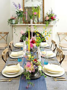 Table with white plates, milk glass and metal vases. Pretty floral combinations.