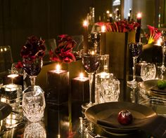 Square tealight holders compliment the nearby clear crystal tumblers and purple crystal wine goblets.