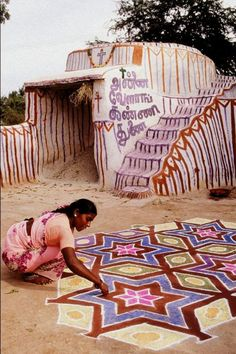 A woman painting a kolam in Tamil Nadu, India.