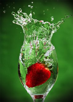 Red and green; dropping a juicy strawberry into a wine glass, splash of water
