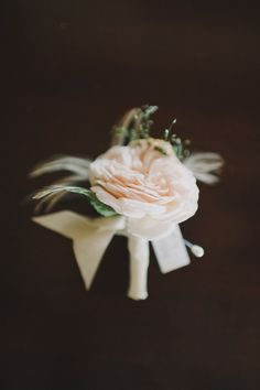 feathery bout with a single rose - photo by John + Louise Weddings - http://ruffledblog.com/ruffled_galleries/modern-film-noir-inspired-wedding/erin_jp-529/