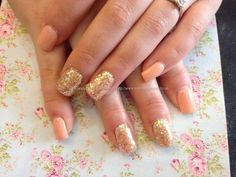Acrylic nails with pastel orange gel polish and gold glitter dust