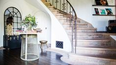 Large entry with industrial center table and curved staircase.
