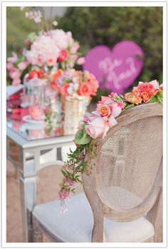Dress up your Bride & Groom chairs with a gorgeous flower embellishment!  Design by Alchemy Fine Events | www.alchemyfineevents.com colorful flowers, flower embellish