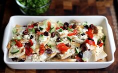 Greek Nachos with Tzatziki by Jessica Smith, parade: This Greek-inspired twist on classic nachos comes together just as easily as the original, but offers a completely different mix of flavors. The pita bread makes a great base, becoming crisp and golden in the oven with a topping of bubbly feta cheese. #Nachos #Greek