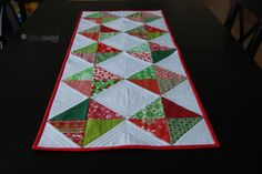 This is a fun table runner pattern with a very classic and simple design. Perfect for a holiday table in the fabrics pictured or swap the holiday fabrics out for more contemporary fabrics and dress your table up year round. #Quilting #Pattern