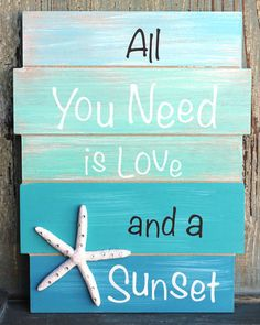 "All You Need is Love and a Sunset Sign This playful decorative sign is painted different shades of beachy blue and green with a little white sparkling starfish in one corner. Approximate measurements: 11.5"" x 9"""