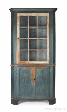 """Lancaster County, Pennsylvania painted pine one-piece corner cupboard, ca. 1790, with an ivory door and rattail hinges, retaining an old blue/green painted surface, 87"""" h., 40"""" w."""