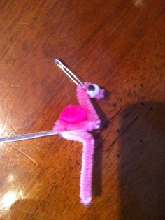 pink flamingo swap made with 1/3 pipe cleaner, 2 googley eyes, one pink puff ball, pin and tag-use hot glue for pink puff ball and 2 googley eyes.