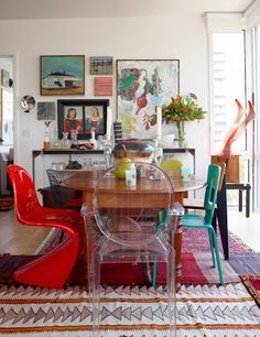 Mixed modern chairs, beautiful rug, great collection of art on the wall.