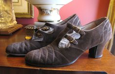 Circa late 20's or early 1930s brown suede t-bar flapper heeled shoes. They have leather soles with metal tips, and brown suede uppers with lots of top stitching and a gimp trim, they each have two thin straps that intersect with a t-bar, and fastened with tiny gilt buckles.