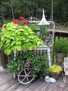 Lovely Garden Vignette....look , this is an old gate a wooden table and the wheel makes it look like some vintage cart. Cool!