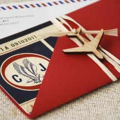 "A vintage style Boarding Pass with an air mail theme is just the ticket! This unique set features a printed sleeve with the words ""Love is in the Air"" and a little wooden airplane embellishment. The RSVP card is a luggage tag and even the envelopes are printed with the air mail theme!"
