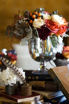 Burnt orange, burgundy, and ivory floral with muted greens in a cracked mercury vase.