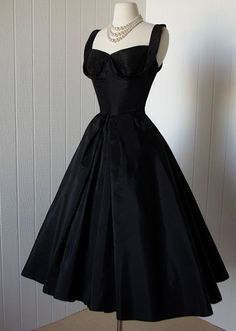 1950's black taffeta Dior-inspired bombshell pin-up cocktail party dress. Classic New Look silhouette with a fitted bodice, vavavoom pleated shelf bust, and a dramatic super full skirt. by Suzy Perette.  -fluid shelf bust continues to shoulders and ends in a gentle fold at her seductive low back  -somewhat stiffer underskirt for form and structure