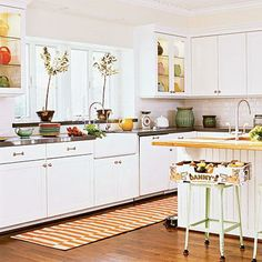 White cabinetry and white tile give this kitchen a light and airy look. Lively vintage accents, such as a farmhouse sink and retro metal barstools, keep the white palette from appearing sterile. Coastalliving.com