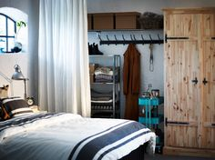 HYLLIS shelving unit in galvanised steel and FJELL wardrobe with 2 doors in solid pine. Full wall closet behind curtain.