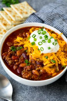 A bowl of Instant Pot chili topped with sour cream, cheese and green onions.