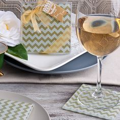 """Chevron is trendy and fashionable and now available in designer glass coaster favors! Classic in design, practical in function these metallic gold chevron pattern coasters will make it to everyone's tables.  Measuring 3.5"""" square and containing non-slip rubber feet these metallic gold and white chevron stripped coasters are a must have for trendy party favors.  The set of 2 coasters in packaged in a clear box with gold organza ribbon and a """"For You"""" tag as shown."""