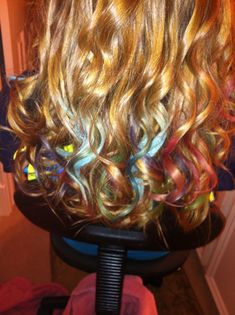 Hair chalking. It's actually done with oil pastels. Just rub the pastel crayon on a small, damp section of hair. Then hit it with the curling iron.