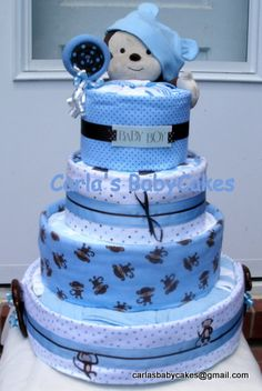 'Blue Monkey' Baby Shower Diaper Cake  Contents:  5 receiving blankets, 1 - 3 piece outfit, 3 bodysuits, 2 bibs, 2 pairs of socks, 1 hat, 1 - 12 inch musical monkey, bottle bank filled with an assortment of other goodies for the baby.