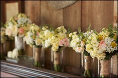Jute wrapped bouquets, place upright in simple vases on mantle - more color over more white -- (more color for margot, more white for bridesmaids), like sweet alyssum and billy balls