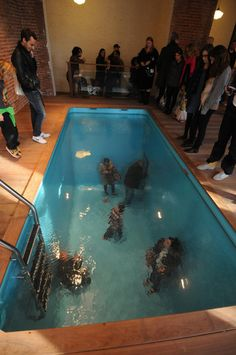 Swimming Pool by Leandro Erlich via artabase: Fully clothed people walk and breathe beneath the surface of this full sized swimming pool. A large, continuous piece of acrylic spans the pool and suspends water above it, creating the illusion of a standard swimming pool that is both disorienting and humorous.