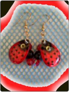 http://diginanchors.com/EarringsAlure_LadyBug - Dangling earrings handmade from fishing lures that is stamped out of pure brass and carefully hand painted. Lady Bug  is beautifully painted red and black with an eye added to give it an eye catching look.The back of the blade is of 22k gold. Elegant black beads and sparkling red crystals are added to enhance the appearance of the earrings. They are 2 inches long and 3/4 inch wide. The earwires are surgical stainless steel and gold plated.