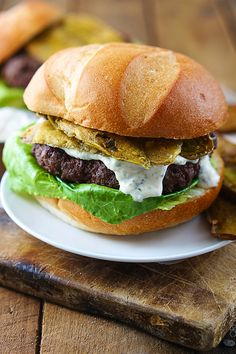Juicy ranch-seasoned hamburgers cooked on the grill, topped with greek yogurt ranch dressing and cajun fried pickles!