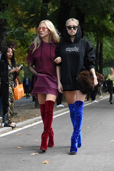 Milan Fashion Week street style | Marie Shea and Caroline Vreeland???s doubled up on fall???s easiest rebel style. Hoodie sweatshirt dresses, are a more youthful take on the common shirtdress style. Simply add an over-the-knee boot for an added on-trend kick, and you???ve got your uniform for a weekend day that leads into a fun night out.