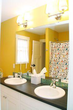 bathroom white cabinets dark countertops and tiled backsplash