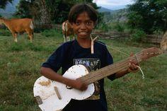 Boy playing home-made guitar in Aidabaleten village, East Timor
