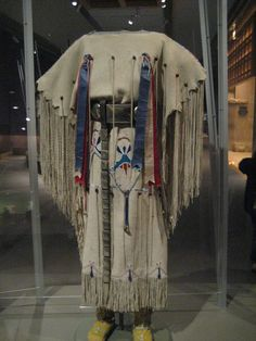 Kiowa Three-Hide Dress    Dress:  c. 1930  Oklahoma  Hide, seed beads, mescal beans, ribbons, sequins, tin cones, sinew  Item number: 13/5854