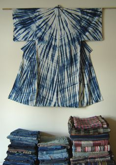 This is a beautiful Korean pojagi suspended in front of a magnificent Japanese 'mino' shibori yukata: the shibori technique is called that because it mimics a mino, or Japanese rain cape.