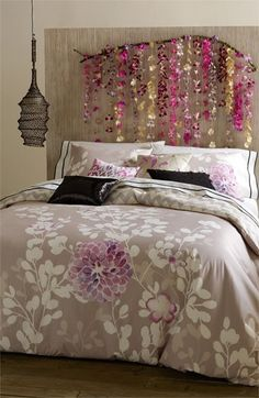 DIY Headboard. Find an interesting branch and mount it to the wall after hanging decorations from it. Pretty!