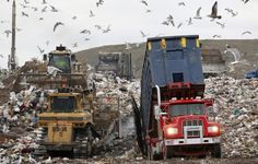 A garbage truck, right, empties its load as bulldozers process the waste at the Central Landfill, in Johnston, R.I.